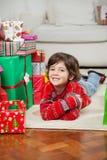 Muchacho feliz que miente además de los regalos apilados de la Navidad Foto de archivo libre de regalías