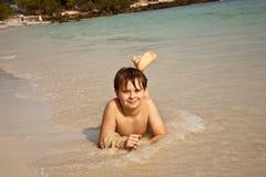 Muchacho feliz que miente en la playa Imagen de archivo