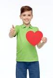 Muchacho feliz que muestra forma roja y los pulgares del corazón para arriba Foto de archivo