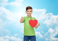 Muchacho feliz que muestra forma roja y los pulgares del corazón para arriba Foto de archivo libre de regalías
