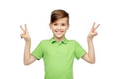 Muchacho feliz que muestra la muestra de la mano de la paz o de la victoria Fotografía de archivo