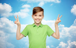 Muchacho feliz que muestra la muestra de la mano de la paz o de la victoria Imagenes de archivo