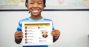 Muchacho feliz que muestra la tableta con el sitio social exhibido en la pantalla Imagen de archivo