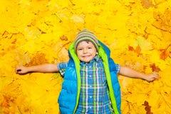 Muchacho feliz que pone en hojas de otoño anaranjadas Fotografía de archivo