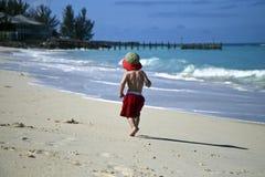 Muchacho feliz que recorre solamente en la playa foto de archivo