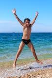 Muchacho feliz que salta en la playa Fotografía de archivo