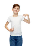 Muchacho feliz que señala el finger a su camiseta blanca Fotografía de archivo