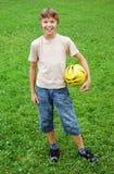 Muchacho feliz que se coloca con la bola Fotografía de archivo libre de regalías