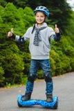 Muchacho feliz que se coloca en hoverboard o gyroscooter al aire libre Imagen de archivo