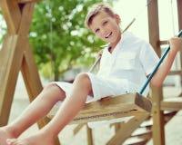 Muchacho feliz que se divierte en un oscilación en un parque del verano Fotos de archivo