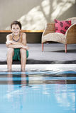 Muchacho feliz que se sienta al borde de piscina Fotos de archivo