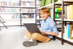 Muchacho feliz que se sienta con el ordenador portátil en el piso Foto de archivo