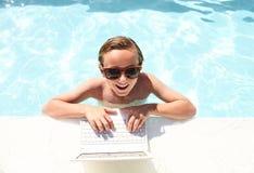 Muchacho feliz que se sienta con el ordenador portátil en piscina Imagenes de archivo
