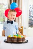 Muchacho feliz que se sienta en Front Of Birthday Cake Imagenes de archivo