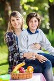 Muchacho feliz que se sienta en Lap At Campsite de la madre foto de archivo libre de regalías