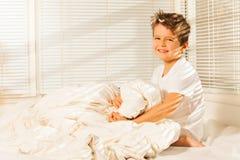 Muchacho feliz que se sienta en su cama con la manta caliente Foto de archivo
