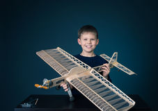 Muchacho feliz que sostiene el aeroplano modelo imagenes de archivo