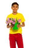 Muchacho feliz que sostiene el cubo con los tulipanes rosados Fotos de archivo libres de regalías