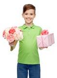 Muchacho feliz que sostiene el manojo de la flor y la caja de regalo Fotos de archivo