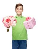 Muchacho feliz que sostiene el manojo de la flor y la caja de regalo Imagen de archivo