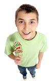Muchacho feliz que sostiene un caramelo del lollipop Imagen de archivo