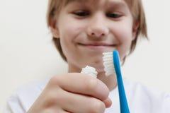 Muchacho feliz que toma la crema dental y que se prepara para cepillar sus dientes con el cepillo de dientes foto de archivo
