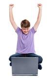 Muchacho feliz sentado con la computadora portátil aislada Fotografía de archivo