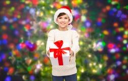 Muchacho feliz sonriente en el sombrero de santa con la caja de regalo Imagen de archivo