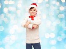 Muchacho feliz sonriente en el sombrero de santa con la caja de regalo Imagen de archivo libre de regalías
