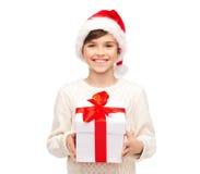 Muchacho feliz sonriente en el sombrero de santa con la caja de regalo Imágenes de archivo libres de regalías
