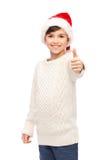 Muchacho feliz sonriente en el sombrero de santa que muestra los pulgares para arriba Imagen de archivo