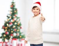 Muchacho feliz sonriente en el sombrero de santa que muestra los pulgares para arriba Imagen de archivo libre de regalías
