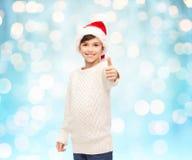 Muchacho feliz sonriente en el sombrero de santa que muestra los pulgares para arriba Fotografía de archivo libre de regalías