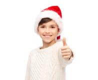 Muchacho feliz sonriente en el sombrero de santa que muestra los pulgares para arriba Imágenes de archivo libres de regalías