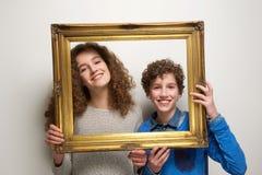 Muchacho feliz y muchacha que llevan a cabo el marco Imágenes de archivo libres de regalías