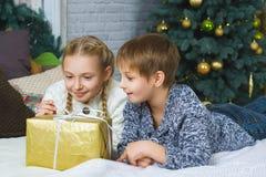 Muchacho feliz y muchacha que mienten en cama Al lado de los regalos Fotografía de archivo