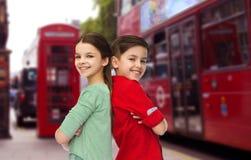 Muchacho feliz y muchacha que se colocan sobre la ciudad de Londres Imágenes de archivo libres de regalías