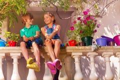 Muchacho feliz y muchacha que se sientan en la barandilla de la terraza fotografía de archivo libre de regalías