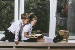Muchacho feliz y muchacha que se sientan en los libros de lectura del alféizar en el th Foto de archivo libre de regalías