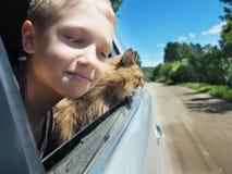 Muchacho feliz y su gato del compañero en el coche imagenes de archivo