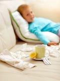 Muchacho frío que miente en la cama, delante de él como limón, té, Imágenes de archivo libres de regalías