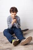 Muchacho fresco que se sienta en su monopatín, sosteniendo un smartphone Fotografía de archivo libre de regalías