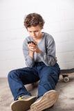 Muchacho fresco que se sienta en su monopatín, sosteniendo un smartphone Imagenes de archivo