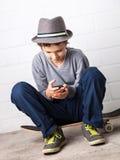 Muchacho fresco que se sienta en su monopatín, sosteniendo un smartphone Foto de archivo libre de regalías