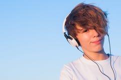 Muchacho fresco sonriente que escucha la música Imagen de archivo
