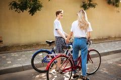 Muchacho fresco y muchacha bonita con el pelo rubio que se coloca con las bicicletas rojas y azules y que lleva a cabo las manos  Imagen de archivo libre de regalías
