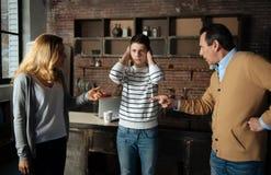 Muchacho frustrado que se coloca entre sus padres Imágenes de archivo libres de regalías