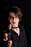 Muchacho gótico con maquillaje artístico que señala su mano Fotos de archivo