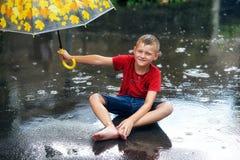 Muchacho gay con el paraguas durante una lluvia del verano fotografía de archivo libre de regalías
