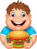 Muchacho gordo de la historieta que come la hamburguesa grande Fotos de archivo libres de regalías